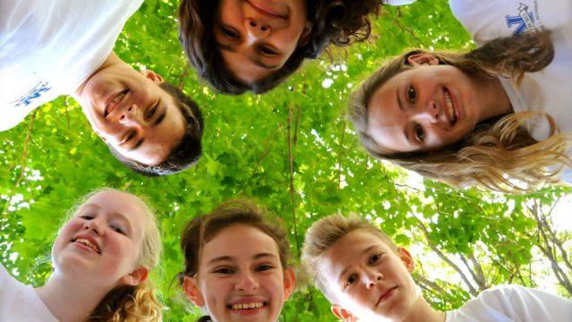 Students in a circle looking down at camera