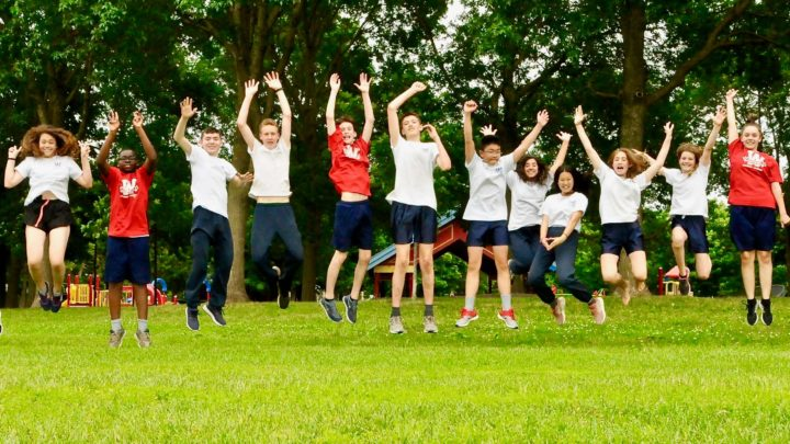 Students jumping in the air and smiling