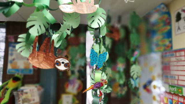 Crafts hanging from string in classroom