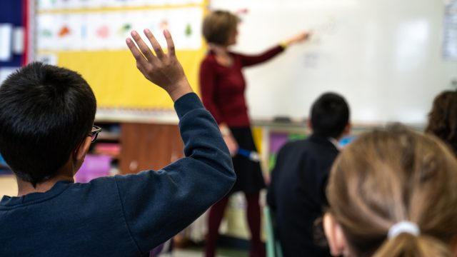 Child raising hand to ask a question in class